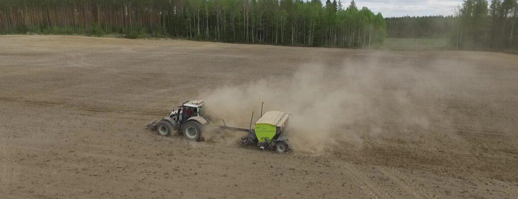 Traktori ja kylvökone pellolla kylvötyössä.